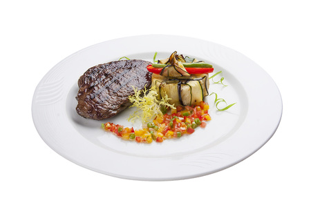 Veal steak with salsa on a white plate