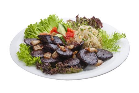 Blutwurst mit Gemüse und Salat. Auf einem weißen Teller