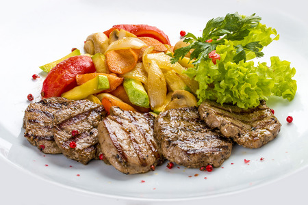 Medallions of veal with vegetables and salad. On a white plate