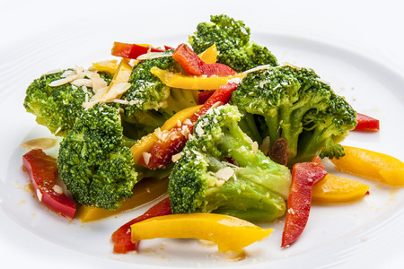 Dietary broccoli with vegetables and peanuts. On a white plate.