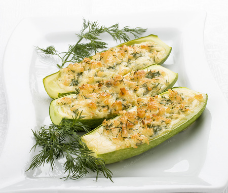 Zucchini stuffed with cheese on a white plate