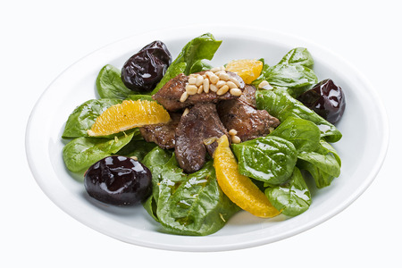 Beef liver with spinach and prunes. On a white plate