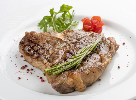 Steak T-bone with greens. On a white plate.