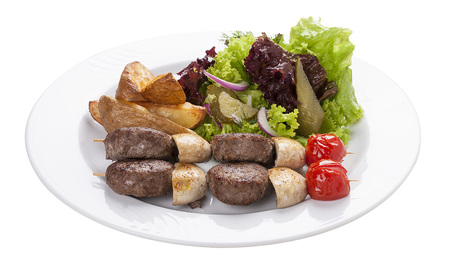 Set of kebabs with vegetable garnish on a white plate Stock Photo