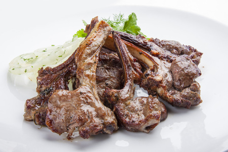 Baked rack of lamb with onions on a white plate