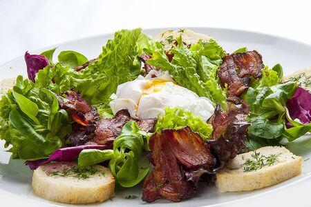 Salade de bacon et œuf poché sur une assiette blanche Banque d'images