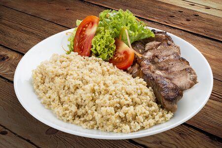 Millet porridge with pork grilled. On a wooden background Stockfoto