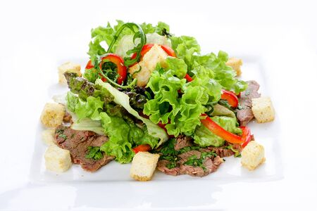 Salad with veal and vegetables on a white plate