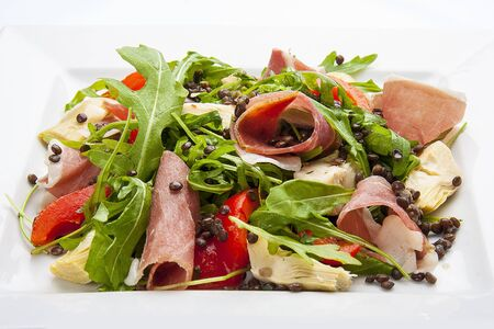 Salad with prosciutto and artichokes on a white plate
