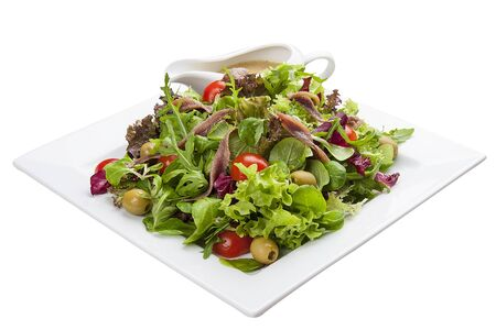 Salad with anchovies and vegetables on a white plate