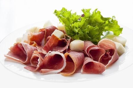Prosciutto with melon on a white plate