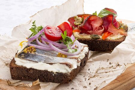 Toasts with venison, pepper and capers, herring and ricotta cheese Stock Photo