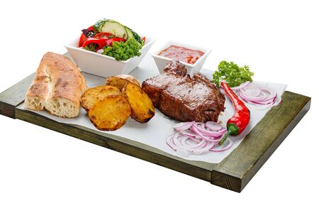 Veal steak with vegetable salad, potatoes and sauce. On a wooden board. 스톡 콘텐츠