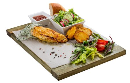 Set of baked chicken fillet, vegetable salad, potatoes and sauce. On a wooden board.