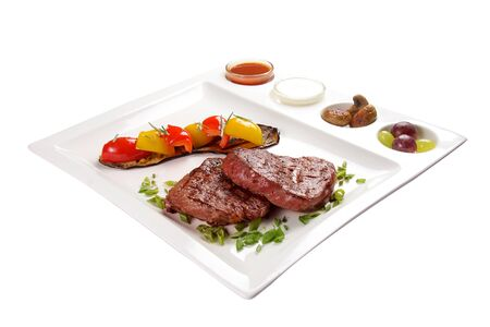 Pork steak with sauces and vegetables. On a white background
