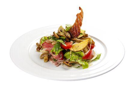 Salad Slavkovsky on a white background. Warm salad with bacon, potatoes, greens and mushrooms