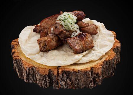 Kebab of pork tenderloin on a wooden slice