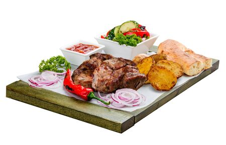 Pork shish kebab with vegetable salad, potatoes and sauce. On a wooden board.