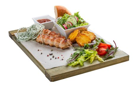 Pork kebab with vegetable salad, potatoes and sauce. On a wooden board. 스톡 콘텐츠