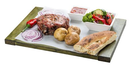 Set of pork steak, vegetable salad, potatoes and sauce. On a wooden board. Chalagach.