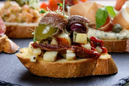 Bruschetta with anchovies, peppers and olives 스톡 콘텐츠 - 128865628