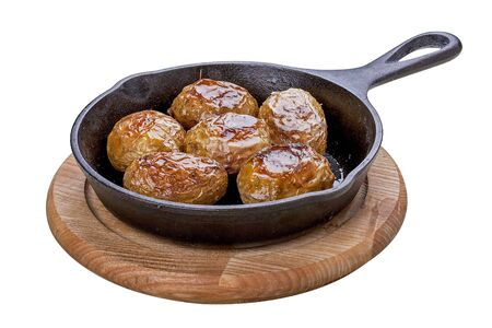 Baked whole potatoes in the pan. On a white background.