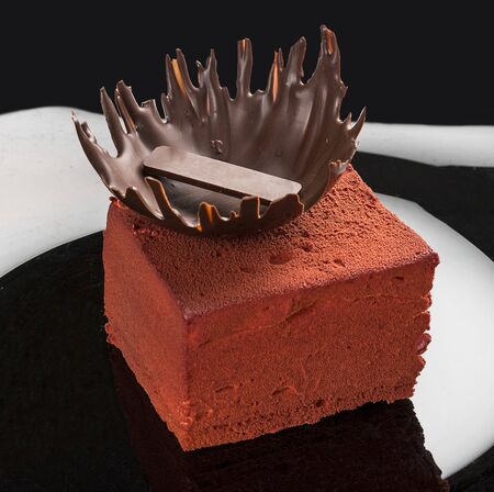 Piece of cake with souffle Birds milk, biscuit, mousse and dark chocolate on dark background