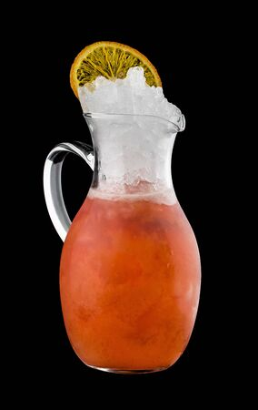Tangerine lemonade in glass jug, on dark background 스톡 콘텐츠