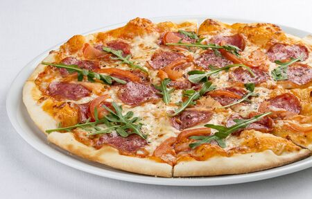Pizza with salami and bell peppers. On a white background