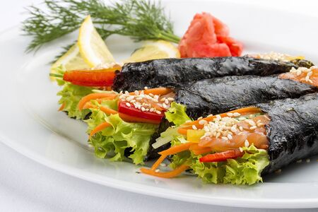 Temaki with salmon and vegetables on white background. Rolls in nori with a filling
