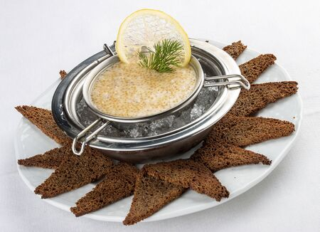 Pike caviar on ice with toast. On white background