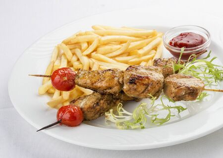 French fries with chicken skewer with red sauce. On white background 스톡 콘텐츠 - 131590572