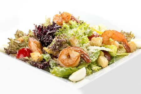 Caesar salad with shrimp. On white background