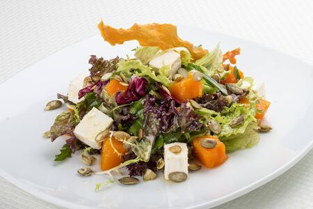 Salad with pumpkin and feta on a white background. Vegetarian 스톡 콘텐츠 - 131591176
