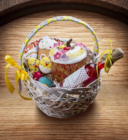 Easter basket with traditional easter cake kulich Ukrainian style with colored eggs and Kagor. On wooden background 스톡 콘텐츠