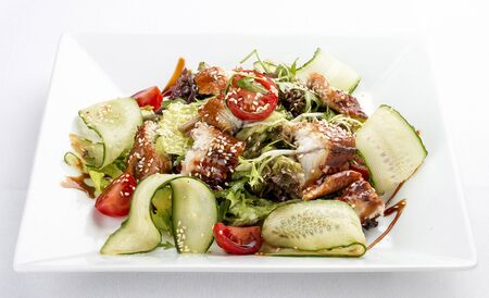 Asian salad with eel and cucumber. On white background