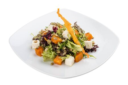 Salad with pumpkin and feta on a white background. Vegetarian 스톡 콘텐츠 - 131604129