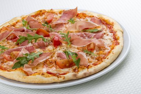 Pizza with prosciutto and arugula. On white background 스톡 콘텐츠 - 131604207