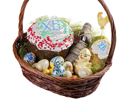 Easter basket with traditional easter cake kulich Ukrainian style with colored eggs and Kagor. On white background