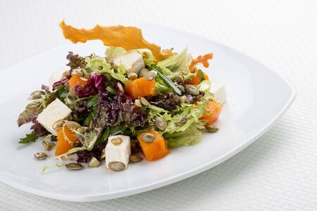 Salad with pumpkin and feta on a white background. Vegetarian