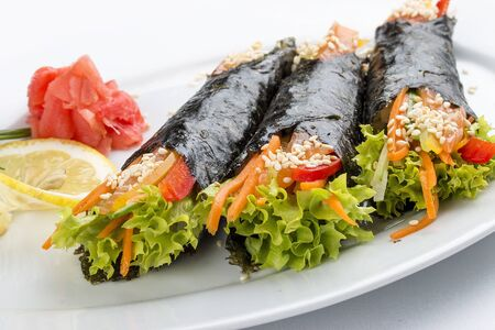 Temaki with salmon and vegetables on white background. Rolls in nori with a filling 스톡 콘텐츠 - 131599381
