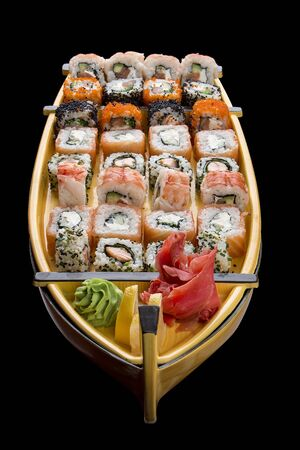 Sushi set in a wooden boat on a black background 스톡 콘텐츠 - 131599371