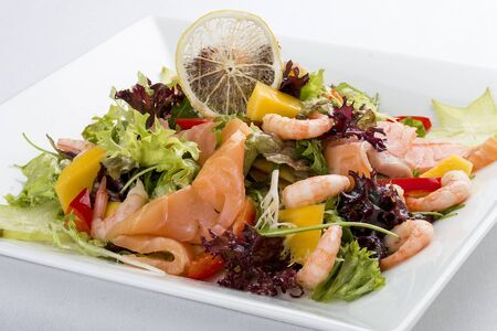 Salad with salmon and shrimp. On a white background 스톡 콘텐츠
