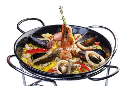 Paella with seafood. The Spanish traditional dish. In a cast iron pan. On a white background