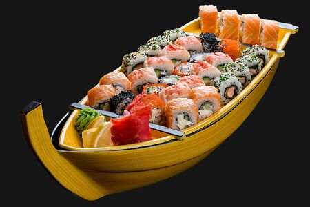 Sushi set in a wooden boat on a black background