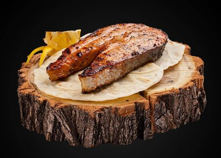 Steak from salmon on a wooden slice