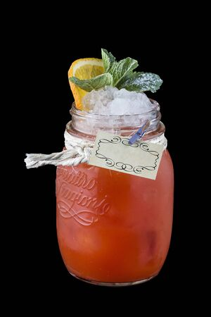 Raspberry lemonade with ginger in a glass jar on a dark background
