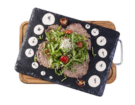 Salad with fried veal and arugula on a stone board. On white background