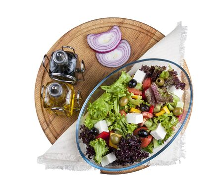 Greek salad on a round wooden Board. The view from the top. On white background