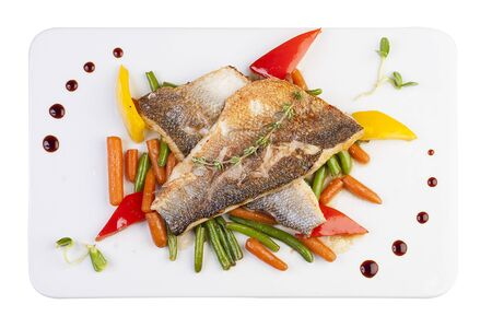 Fillet of sea bass on the vegetables. On white background 스톡 콘텐츠